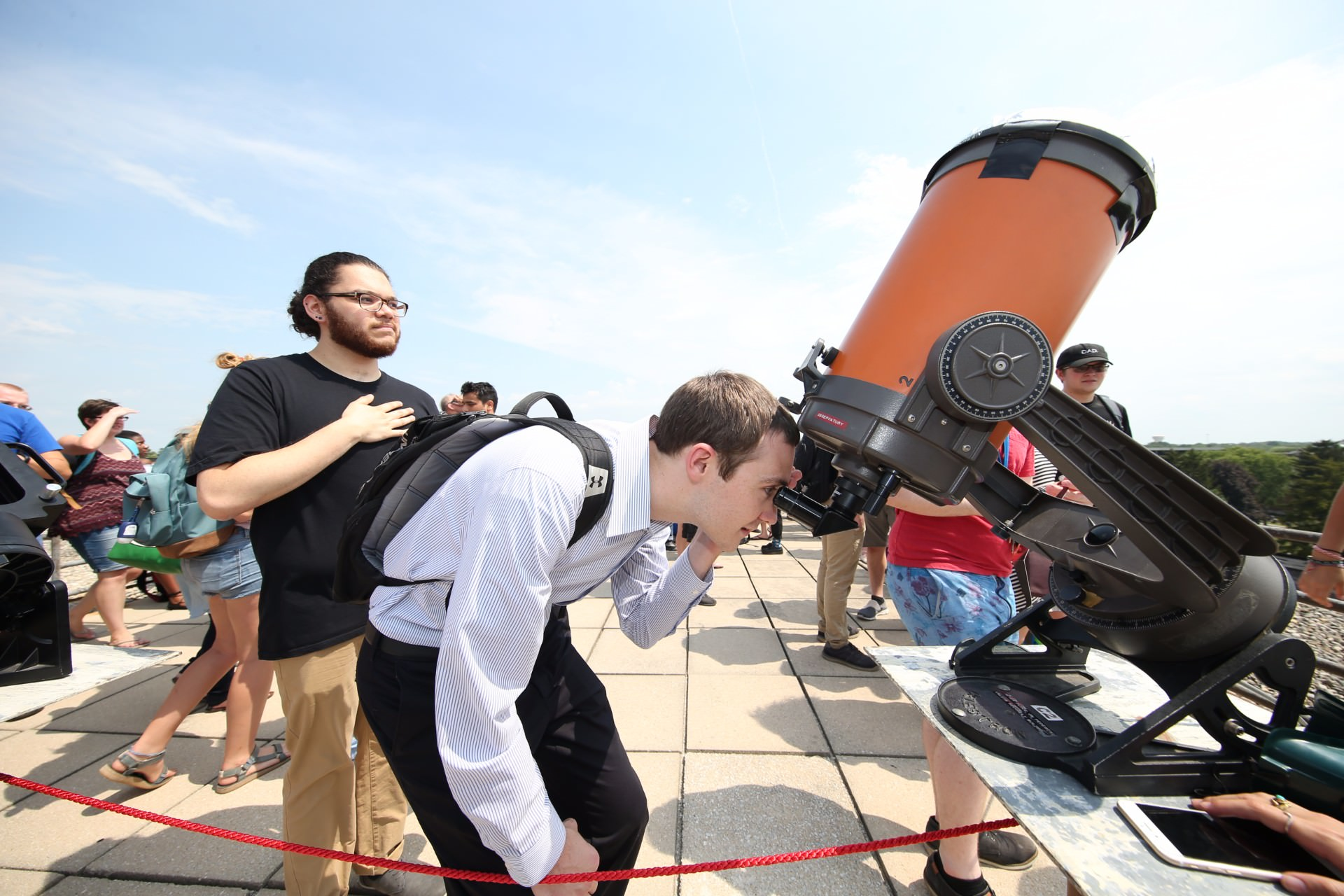 man wearing backpack while looking into telescope