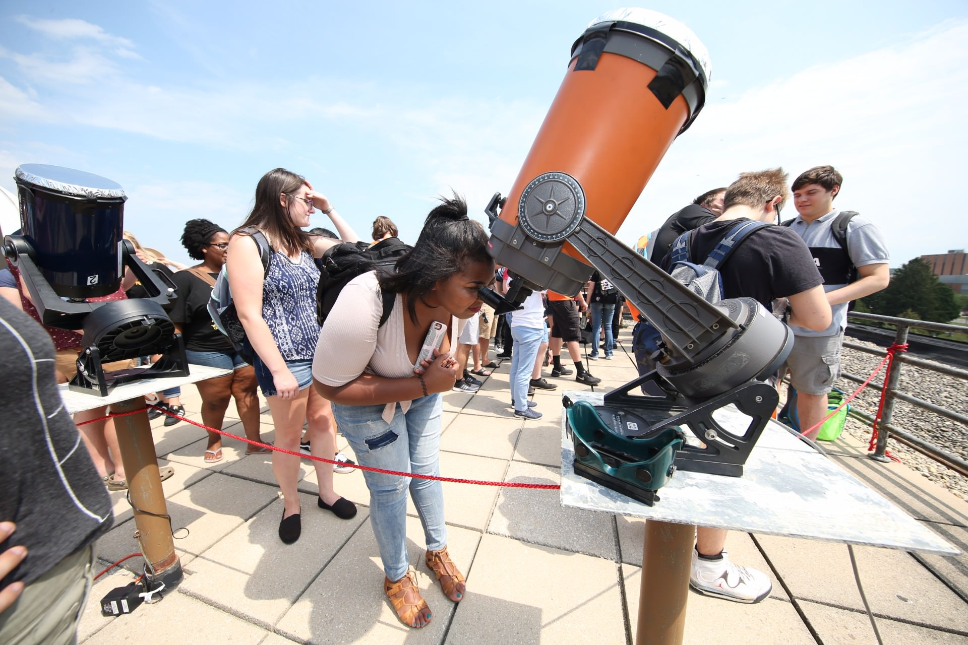 woman looking into telescope