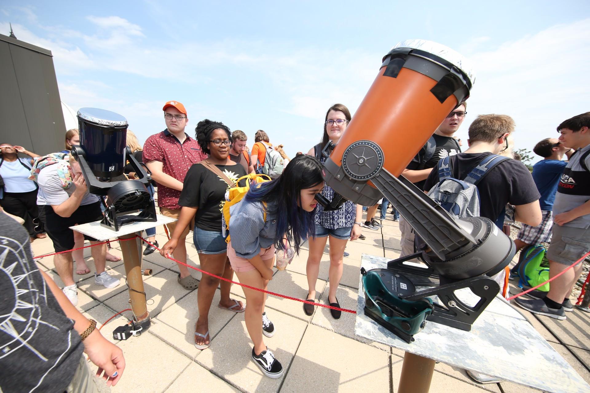 woman wearing vans looking into telescope