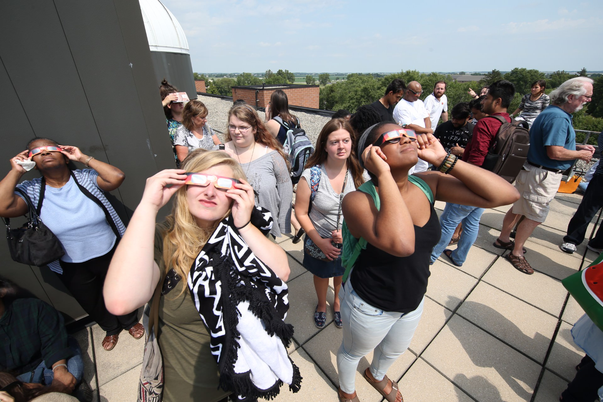 group of people looking at solar eclipse