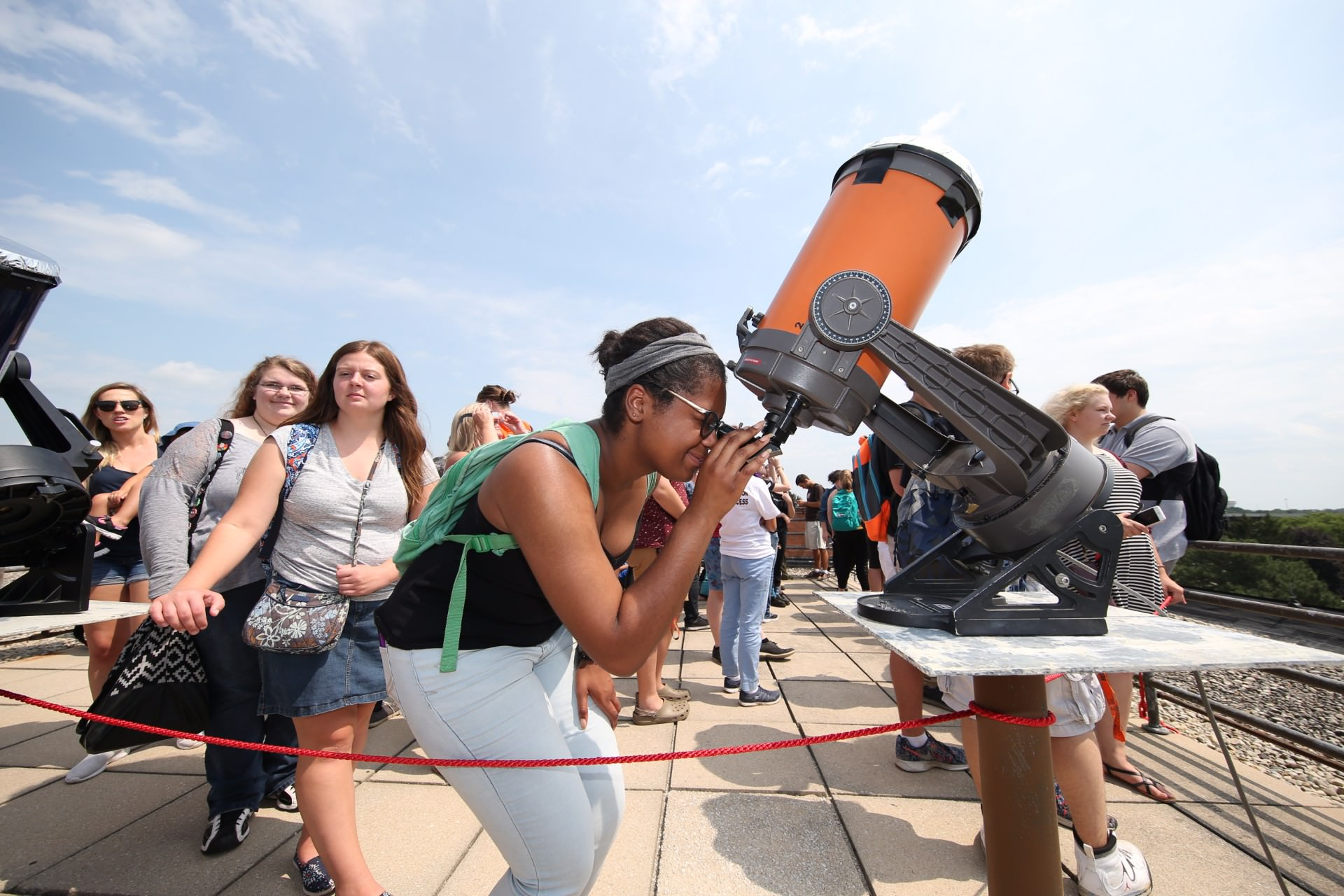 woman with green backpack looking into telescope