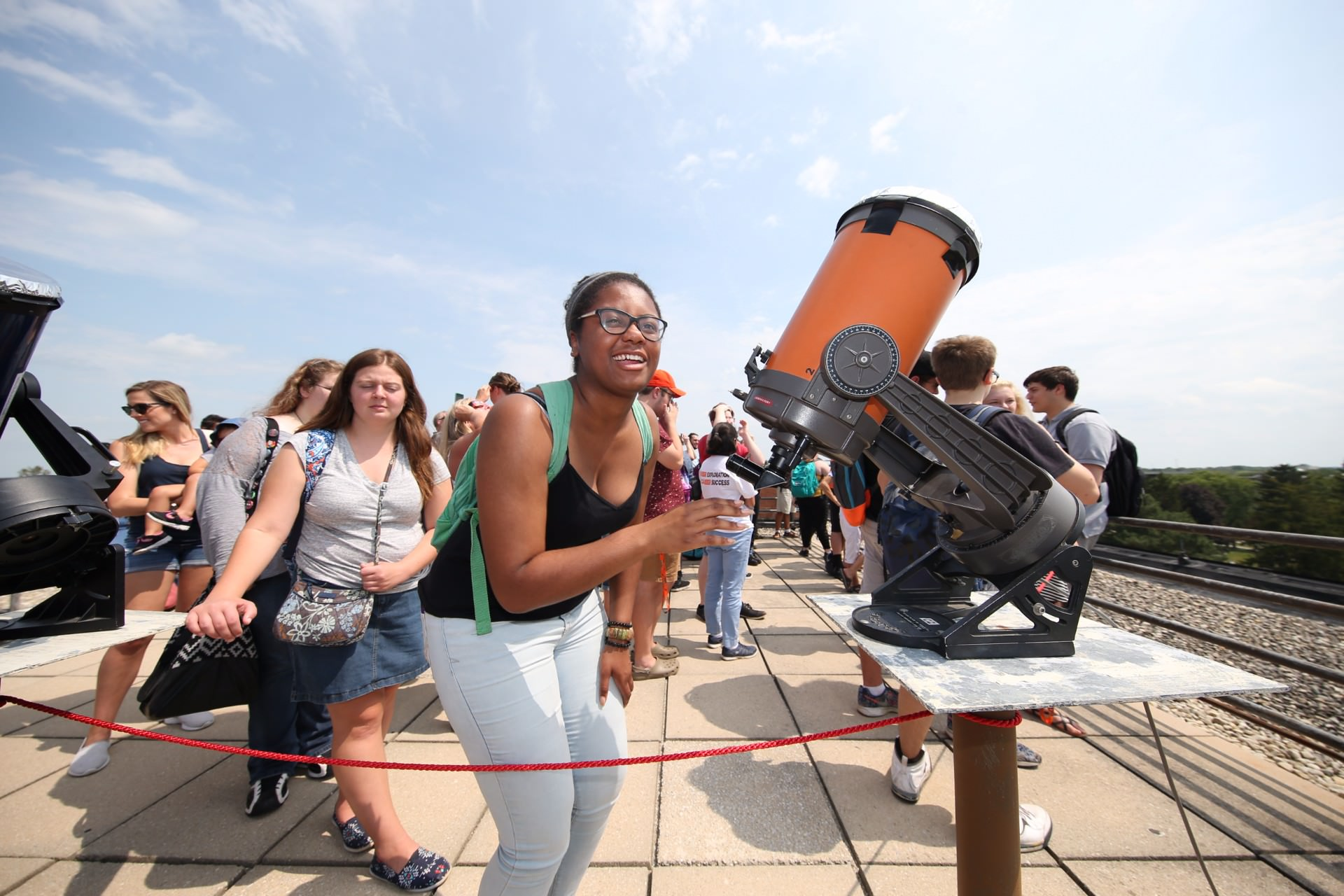 girl smiling at camera next to telescope