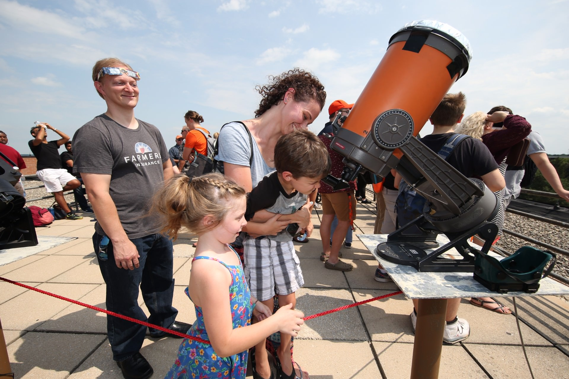 family looking into telescope