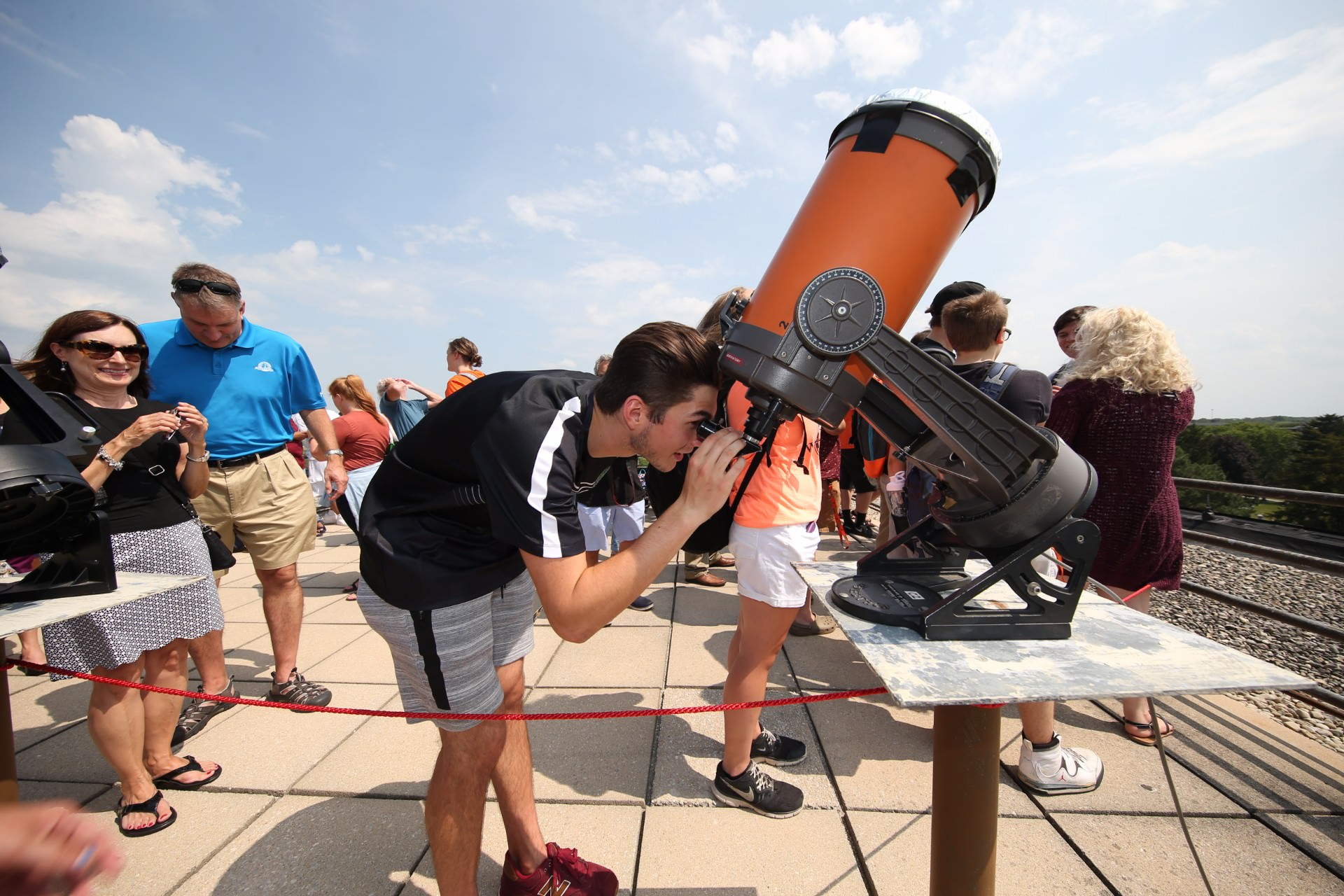 guy wearing black shirt looking into telescope