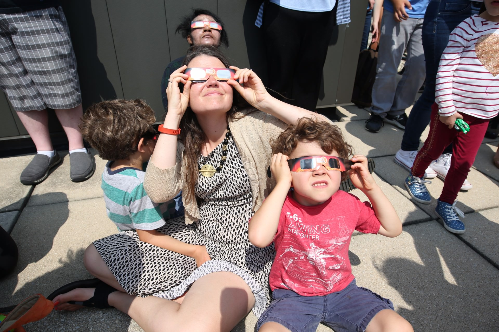 woman with kids looking at solar eclipse