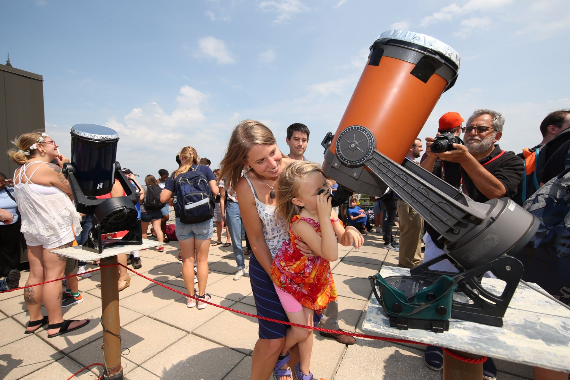 small child looking into telescope