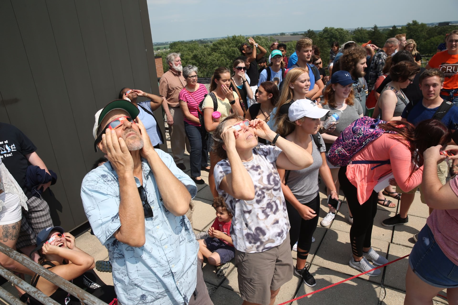 people looking at solar eclipse on rooftop