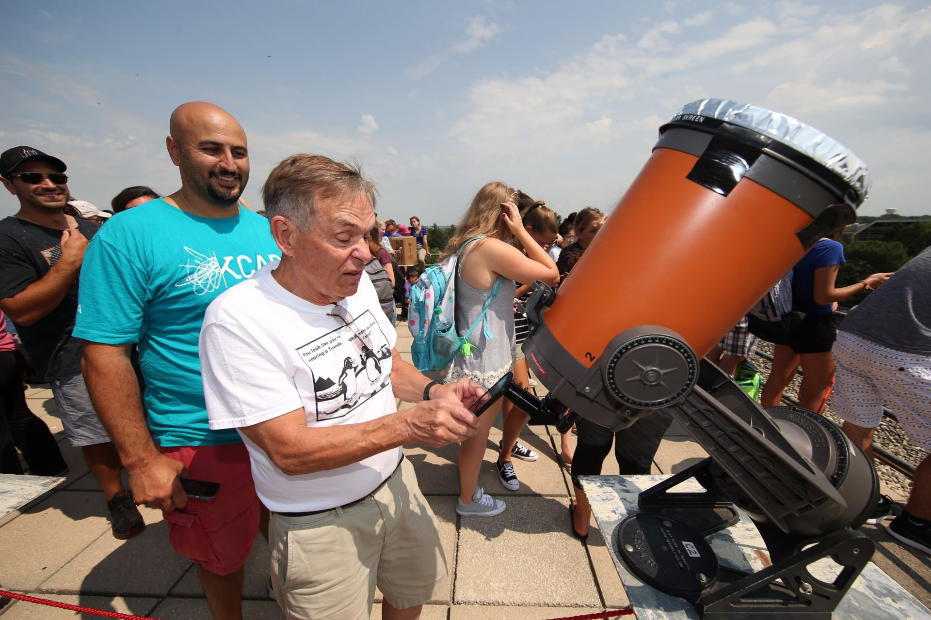 man taking picture of telescope eyepiece