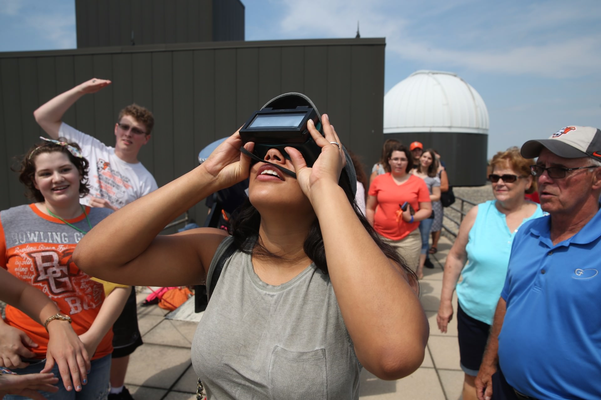 woman wearing goggles while looking at solar eclipse