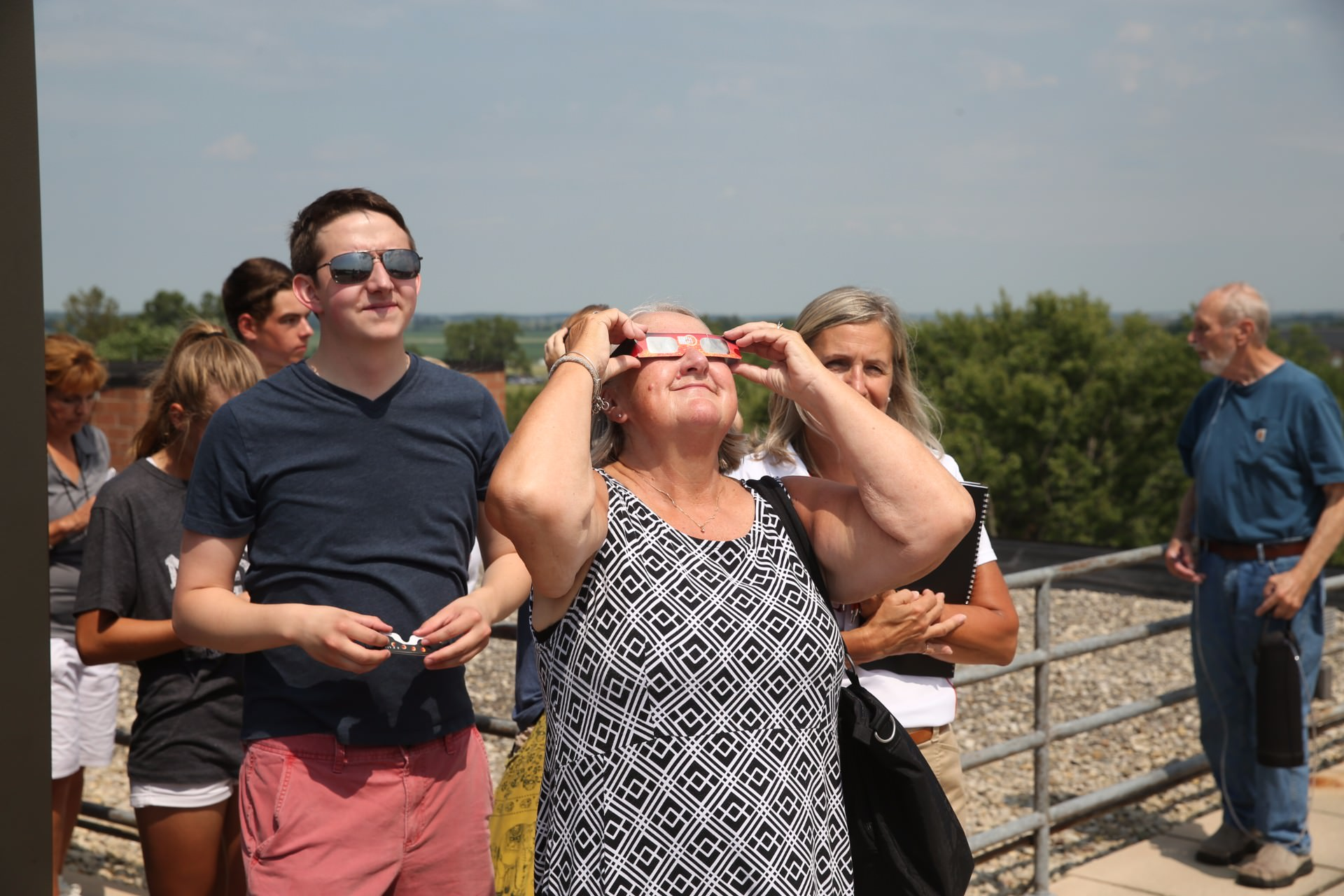 Woman wearing white and black dress while looking through glasses at the sky