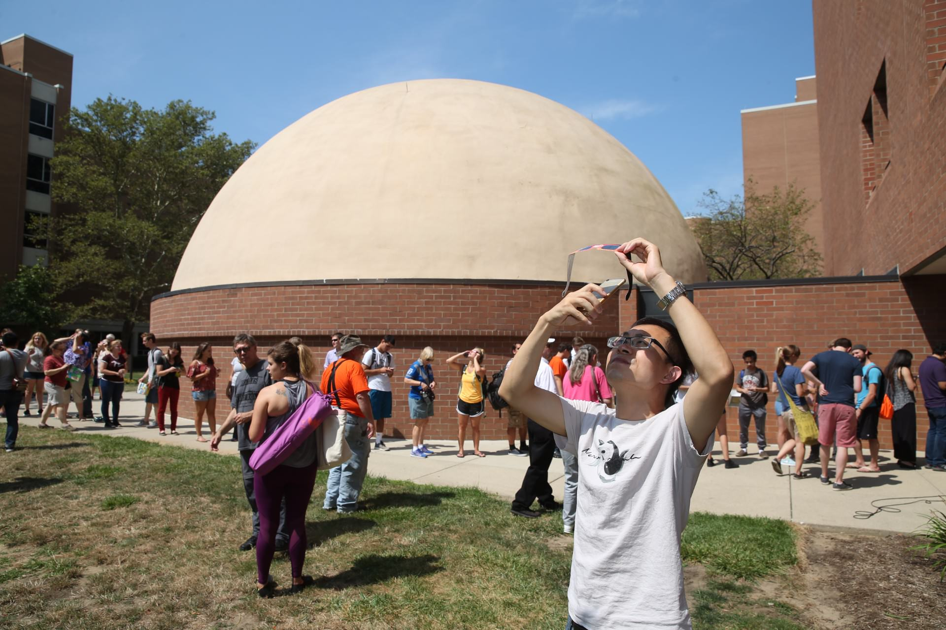 Group of people outside observatory looking up at solar eclipse