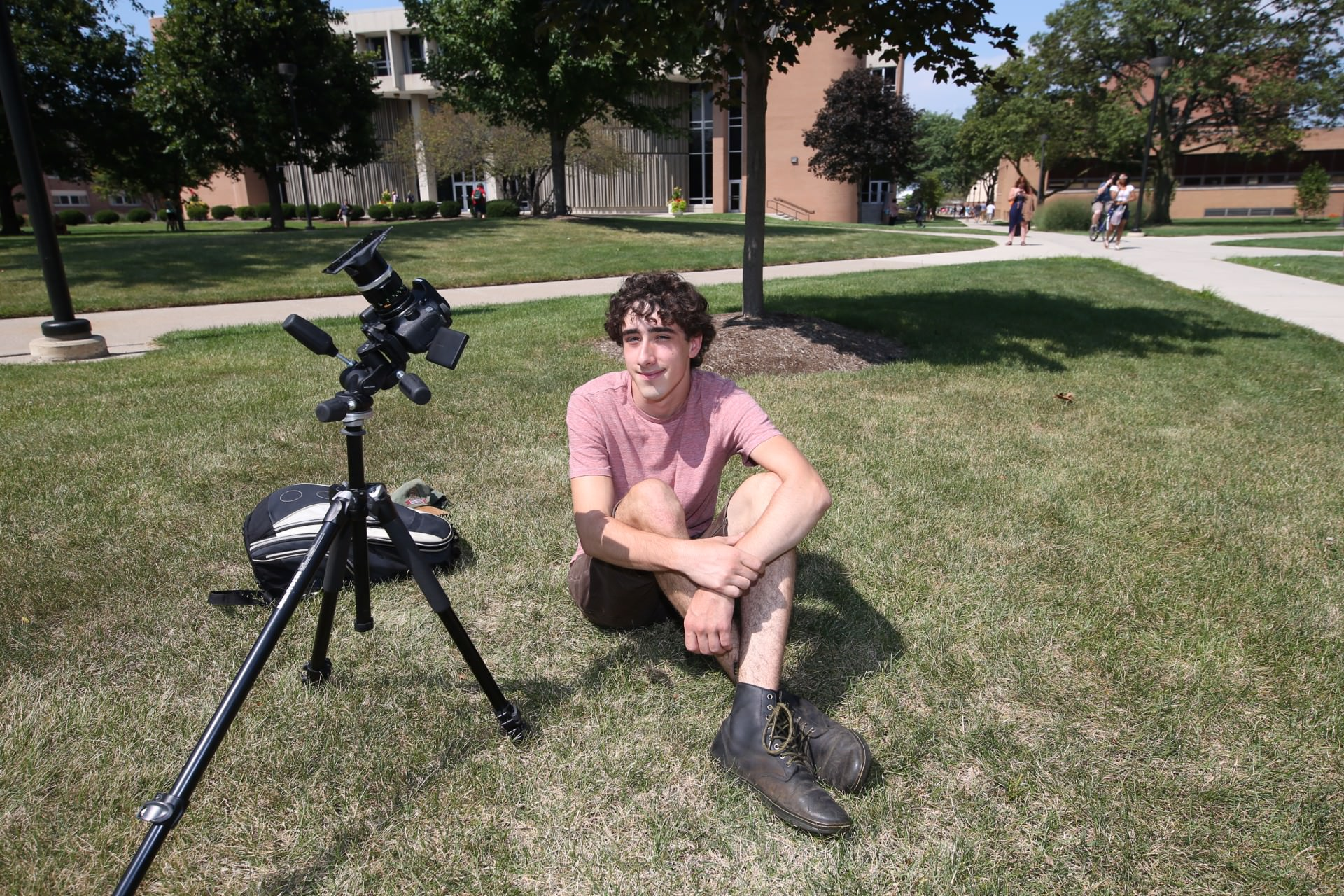 Young man sitting on grass next to camera