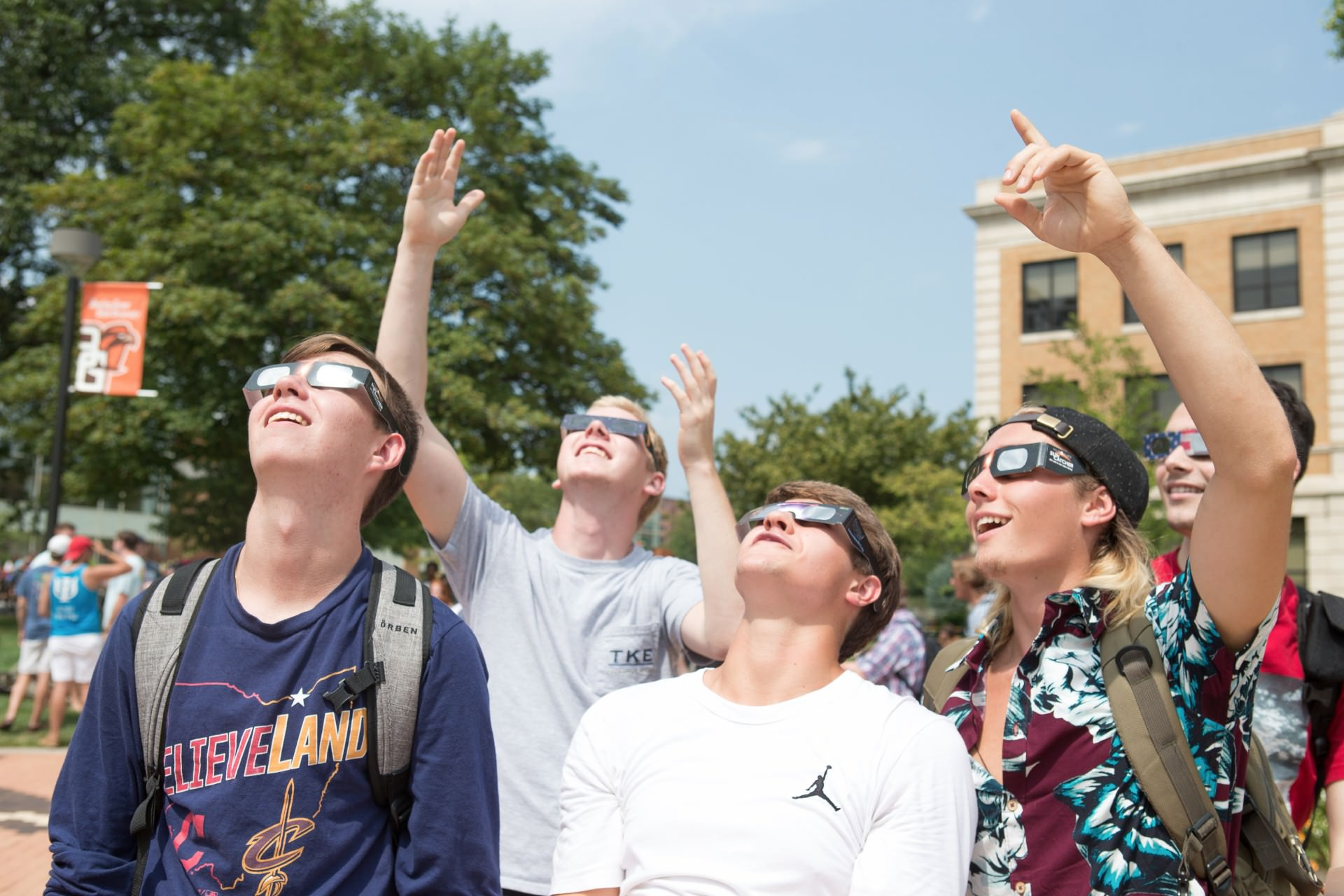 Group of male students pointing up at the sky wearing solar eclipse glasses