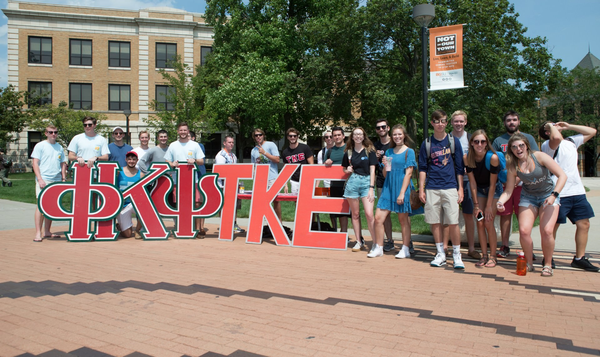 Group of students standing near fraternity sign