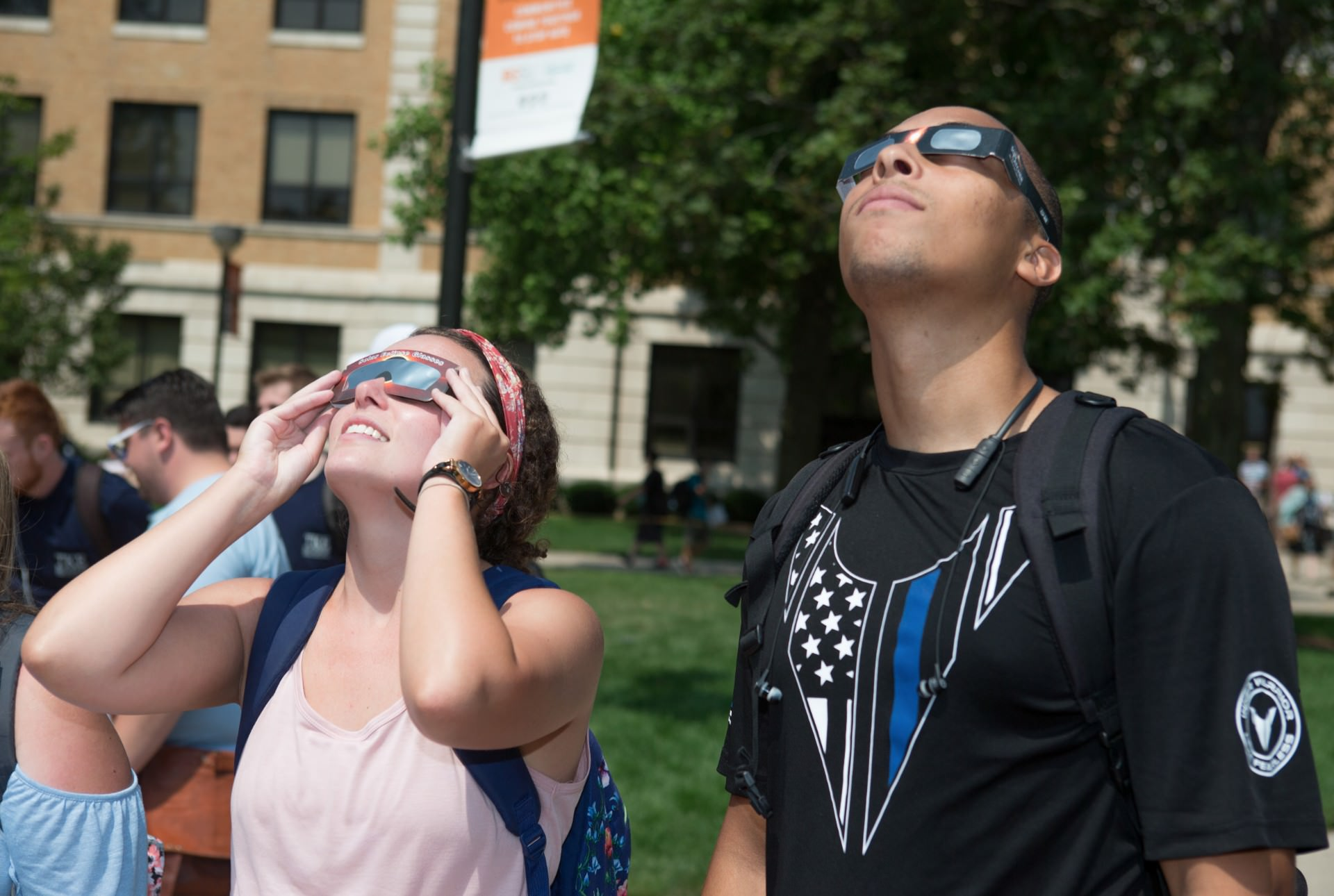 Two students looking up at sky wearing solar eclipse glasses