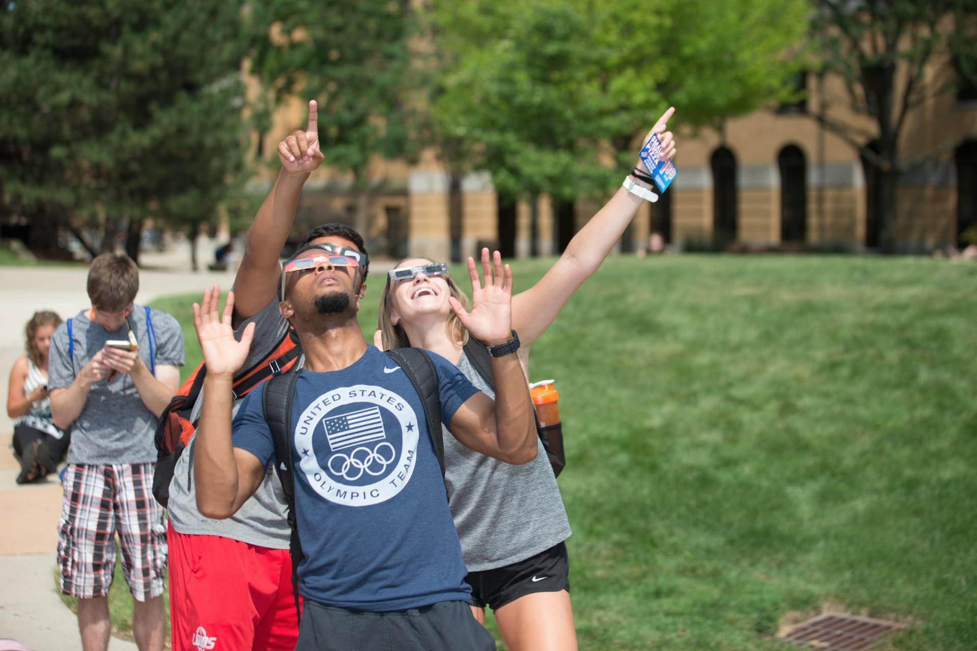 Students pointing at sky while looking up wearing solar eclipse glasses