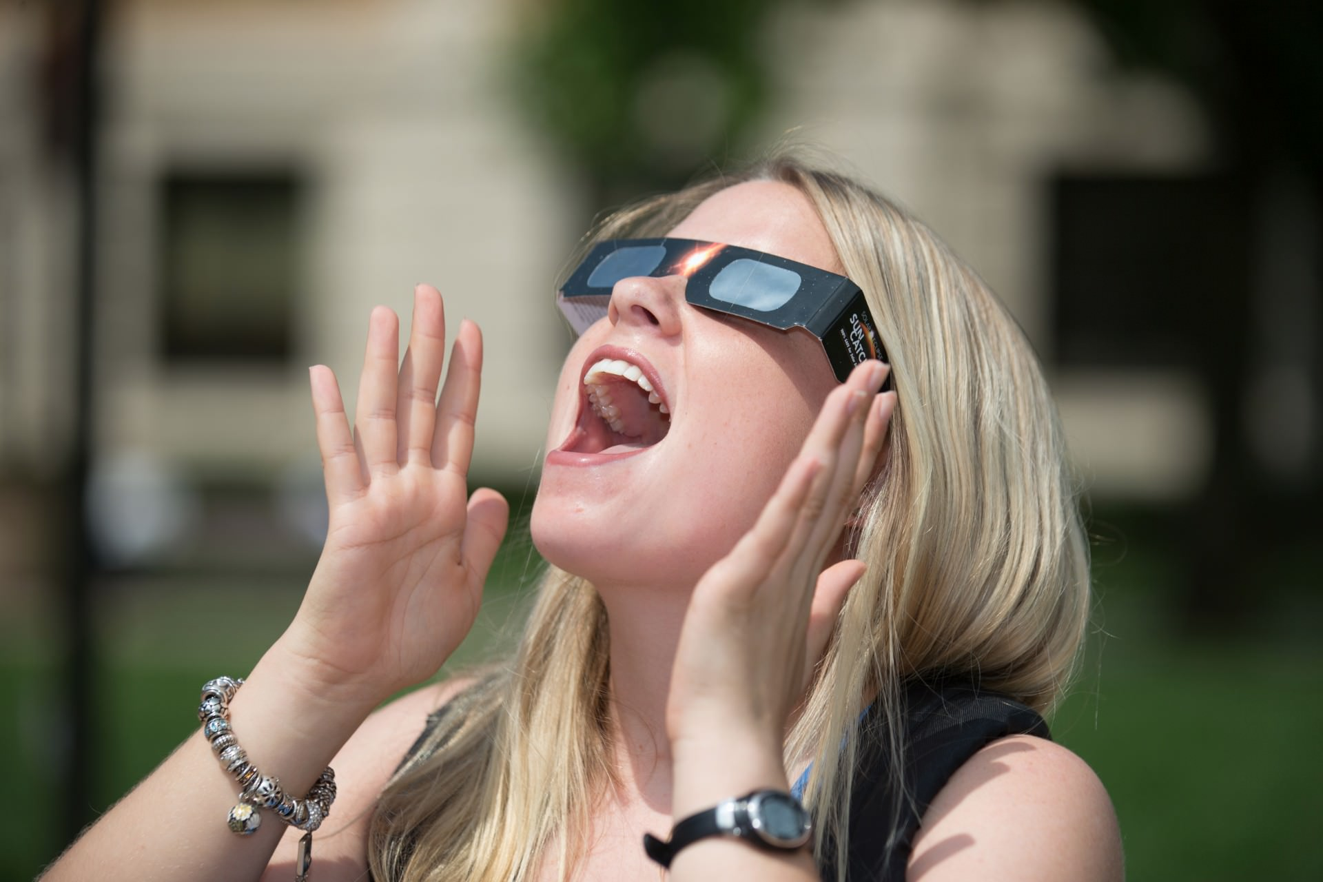 Close up of surprised girl looking up wearing solar eclipse glasses