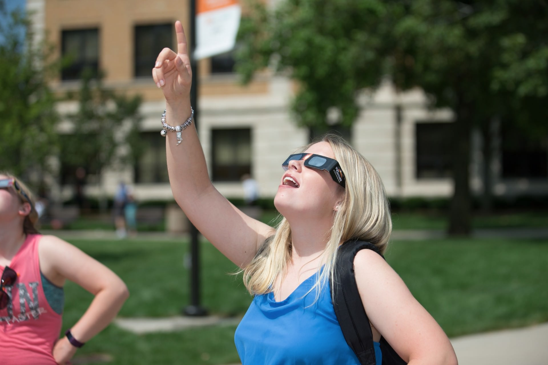 Close up of surprised girl pointing up wearing solar eclipse glasses