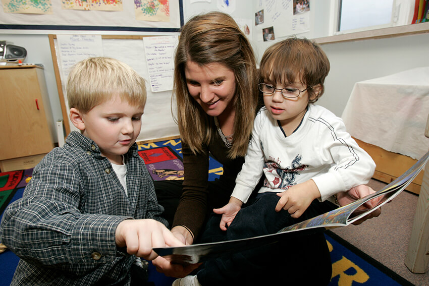 Teacher reading to two young students