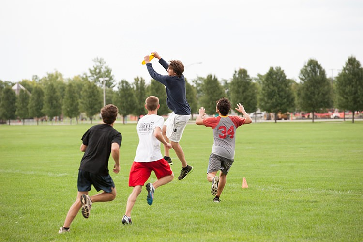 students playing frisbee on IM field