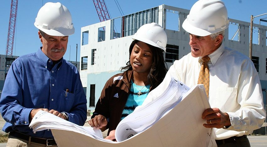 Photo of two graduate professors working with a graduate student on a job site