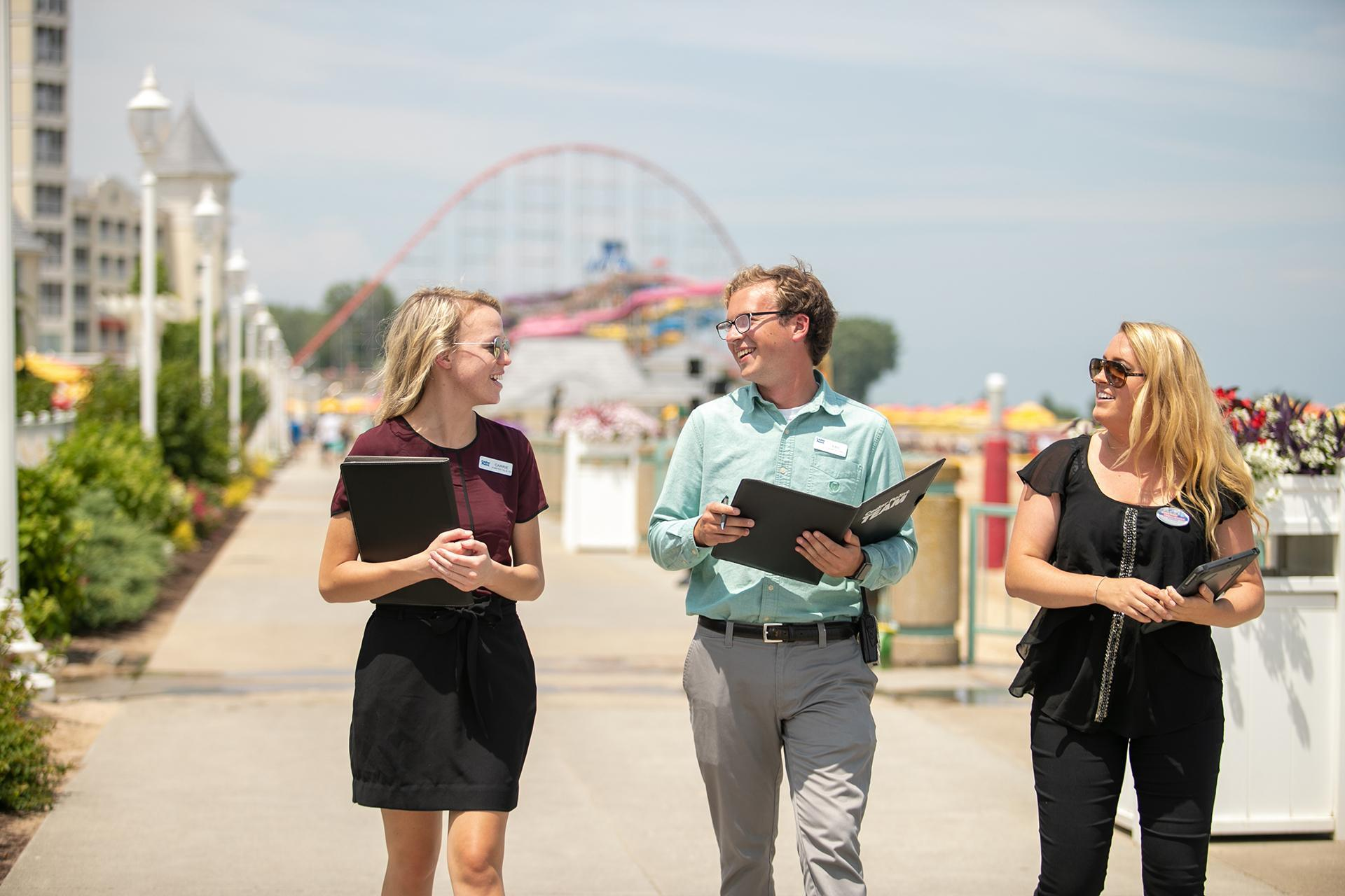BGSU resort and attraction management students walk through the Cedar Point resort and theme park on a sunny day.