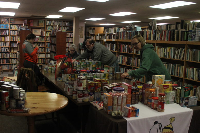 This is a photo of people sorting cans for the food drive