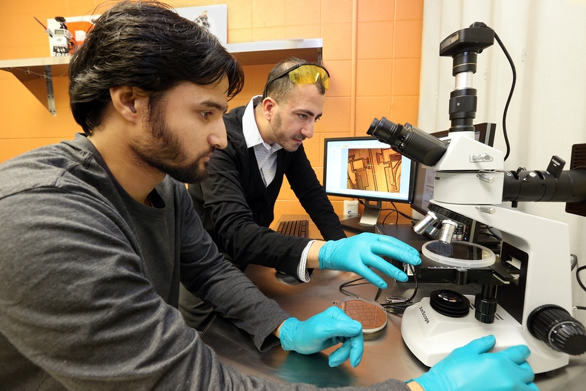 A professor guiding a student while they work with a microscope