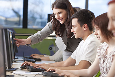 Teacher-using-computer-with-student