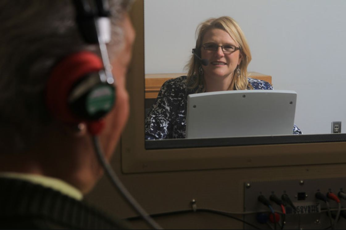 A man sits inside a booth with headphones on. He is having his hearing tested. A smiling audiologist sits outside the booth, visible through a glass window.