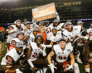 Members of the  BGSU Falcon football team celebrate the 2015 MAC Championship win with President Mary Ellen Mazey.