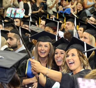 Angelica Mormile, right, takes a selfie with her friends as they celebrate August Commencement at The Stroh Center.