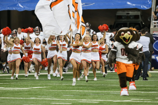 The BGSU Falcon Cheerleaders lead the football team onto the field for the start of the 2015 Marathon Mid-American Conference Championship Game at Ford Field in Detroit, Mich.