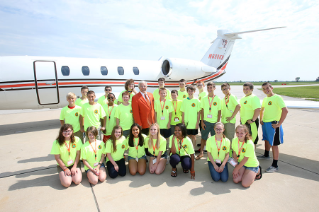 Campers at Falcon Millionaires joined J. Robert Sebo '58, '13 (Hon.) center, former chair of BGSU Board of Trustees and retired senior vice president for Paychex Inc., on a tour of his jet. BGSU hosts a one-week financial camp, Falcon Millionaires, each summer in June.