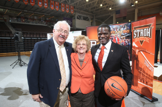 Former Board of Trustees Chair Francis C. (Fran) Voll and President Mary Ellen Mazey welcome new head men's basketball coach Michael Huger '94.