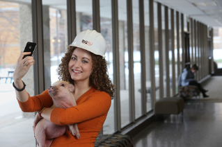 Alumni Laureate Scholar and construction management major Amey Hewitt '15 raised money for a service project when people donated to be able to take pictures with her miniature pig.