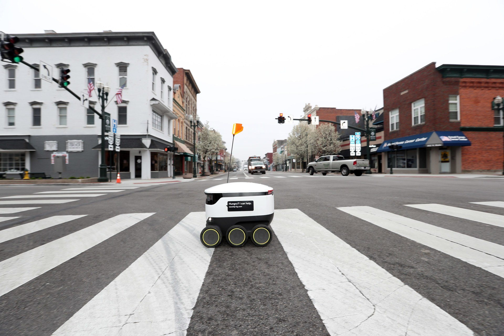 Starship robot crossing main street in crosswalk