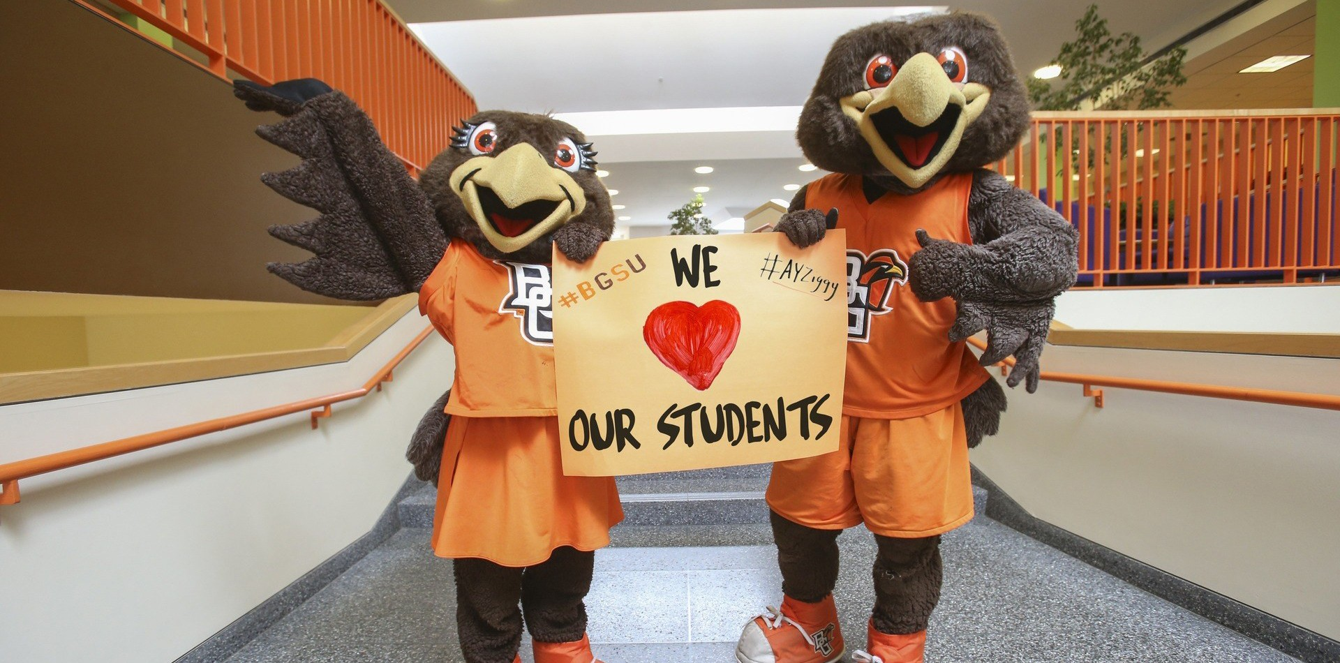 Freddie and Frieda holding we heart our students sign