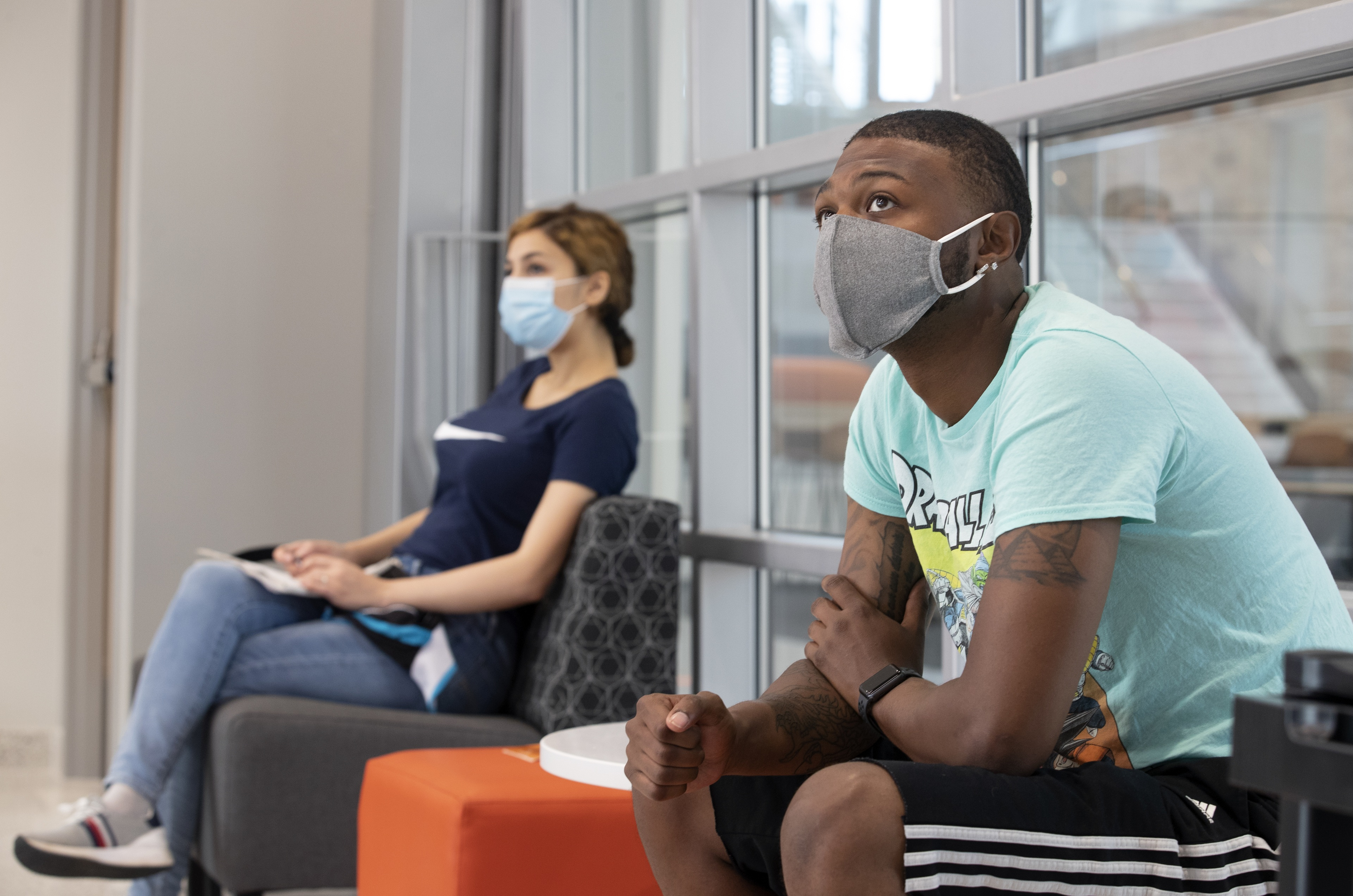 Two students sitting on campus with masks on