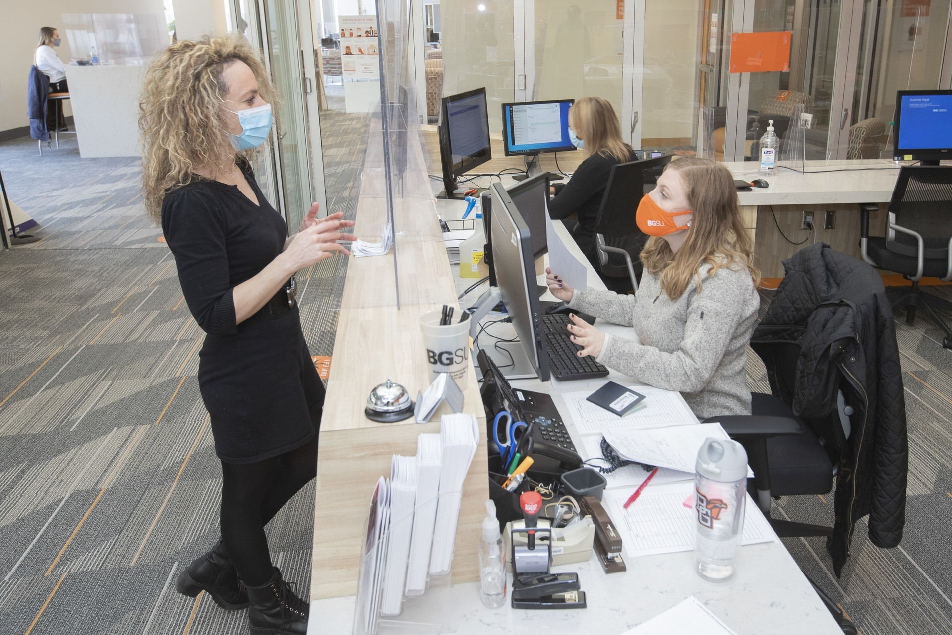 A female wearing a facemask speaks through plex-glass to a masked female employee at the BGSU Career Center.