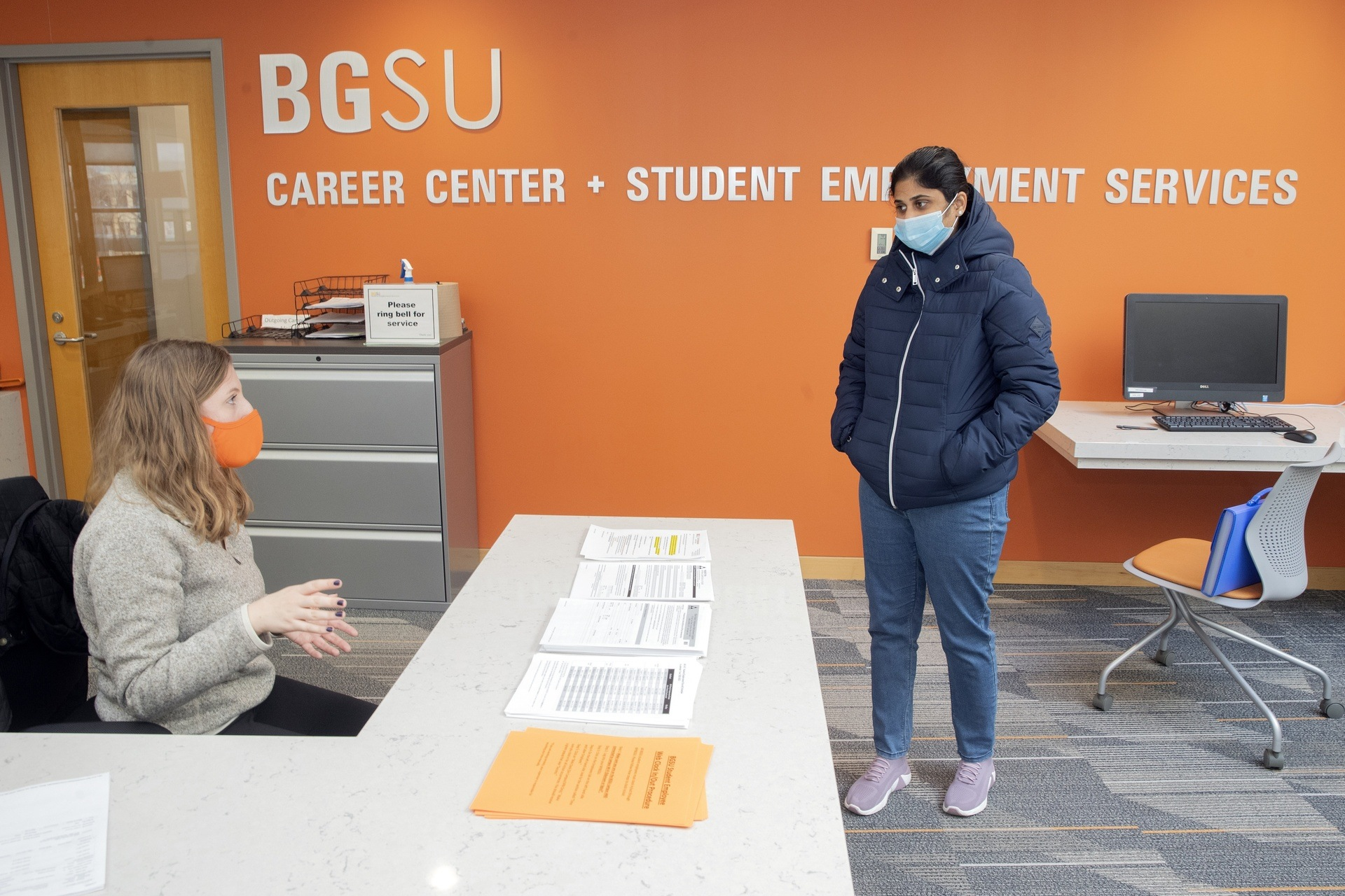 A female student wearing a facemask chats with a masked female employee of the BGSU Career Center at the front desk