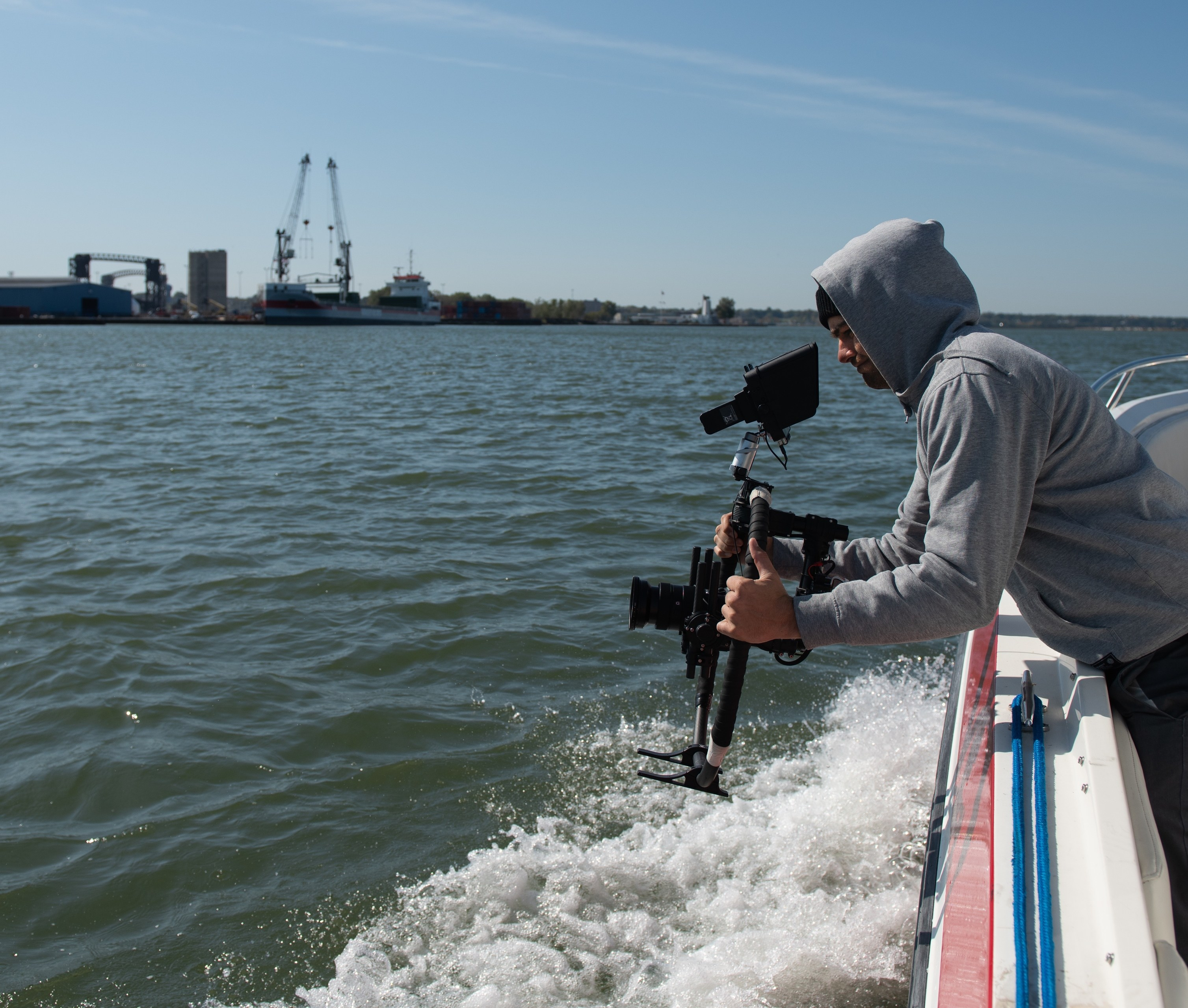 Chad Butler films the Cuyahoga River shoreline for a redevelopment project.