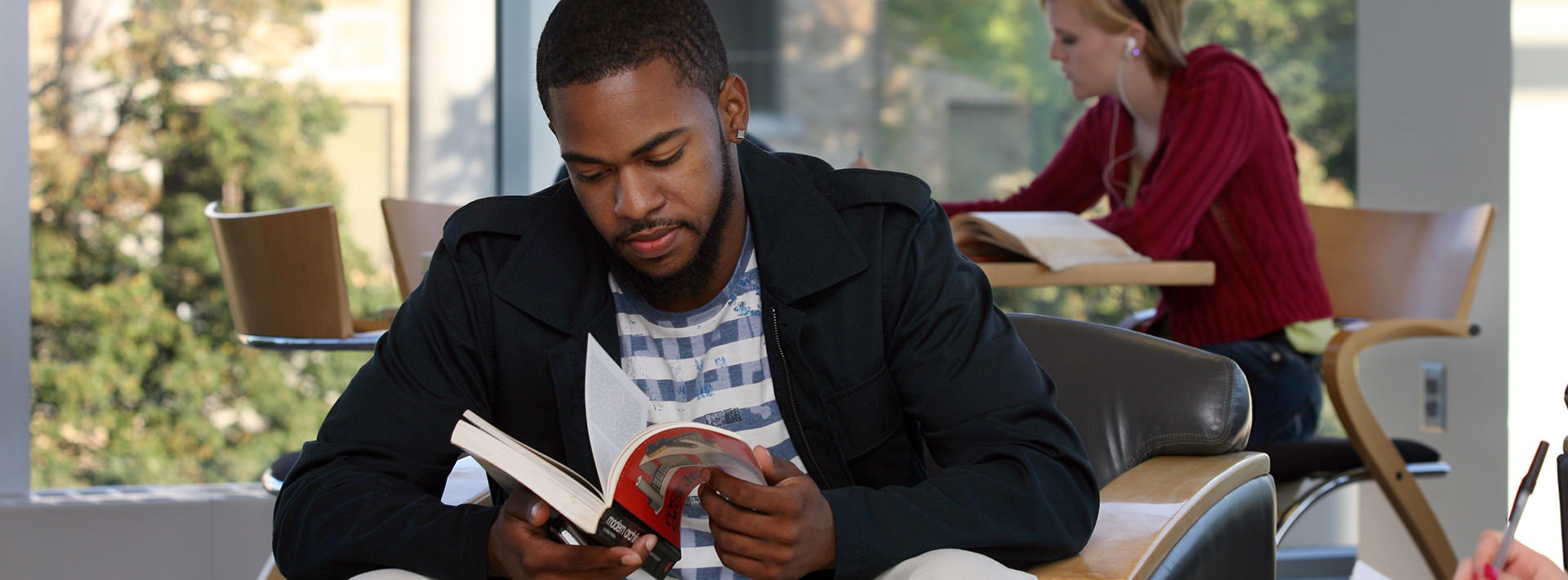 A male student flipping through a book.