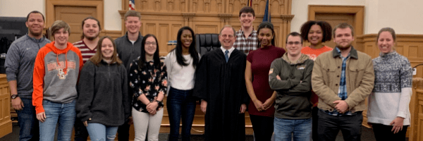 Students in a courtroom smiling with a Judge