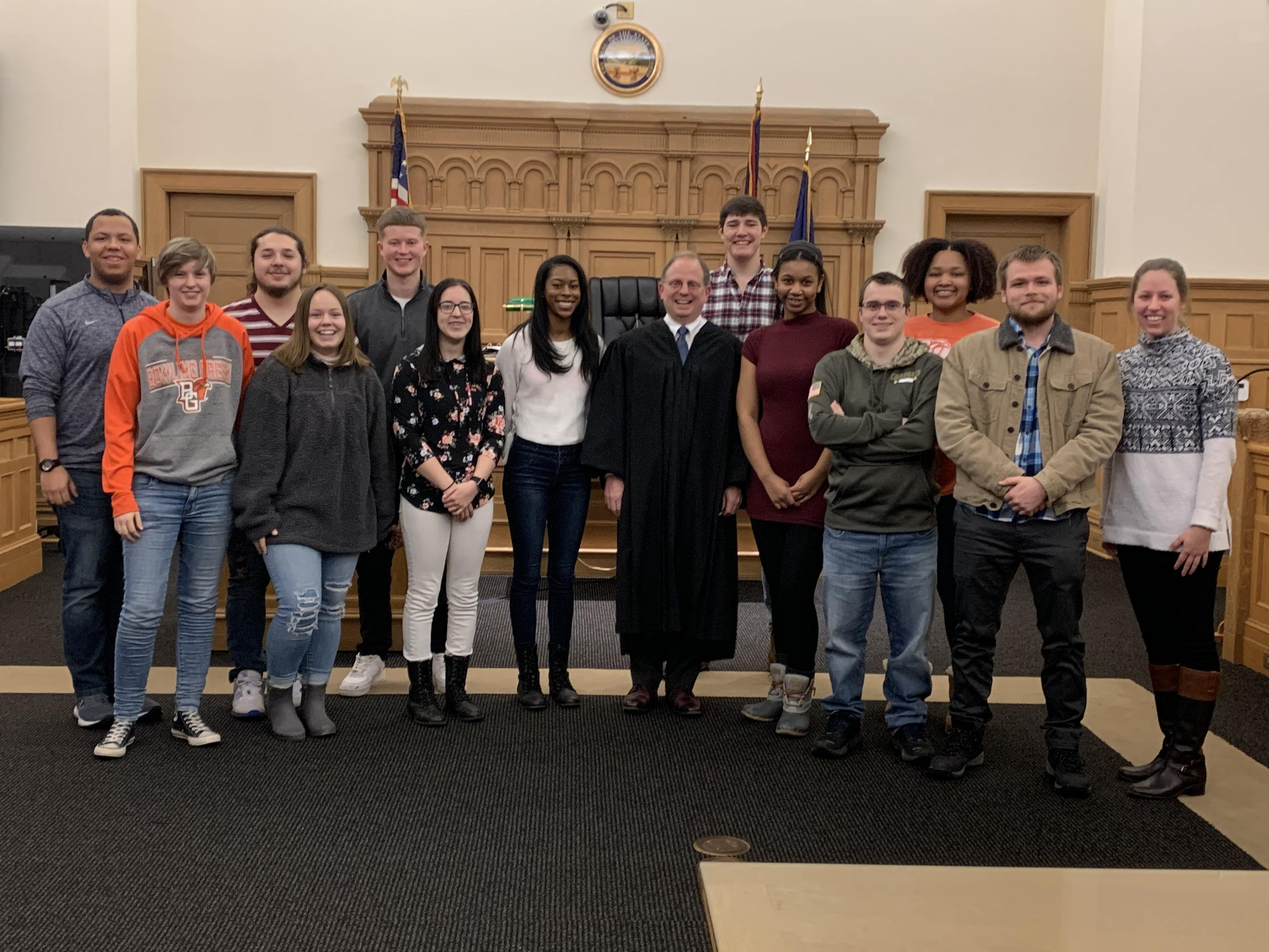 Students on a field trip, smiling with a Judge in a courtroom