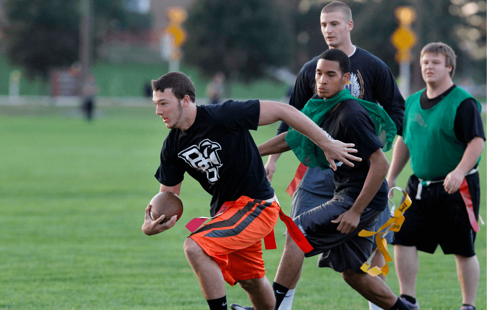 Four students playing flag football